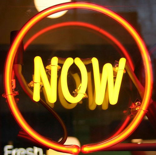 Neon sign that reads 'NOW'.