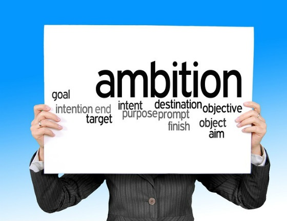 A person holding a sign that reads 'ambition', along with several synonyms.