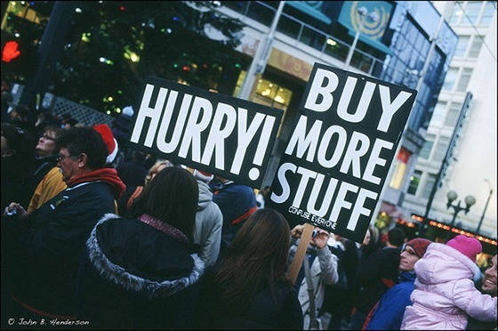 """A crowd of people, two of whom are holding placards reading """"Hurry!"""" and """"Buy more stuff!""""."""