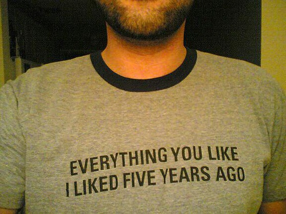 A man wearing a shirt with the slogan 'Everything you like, I liked five years ago'.