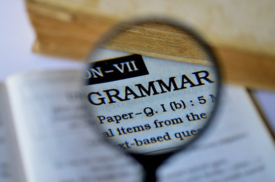 Magnifying glass showing the word 'Grammar'.