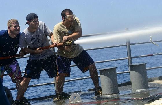 Sailors manning a firehose.
