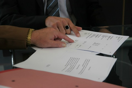 Two businesspeople pointing at a contract.